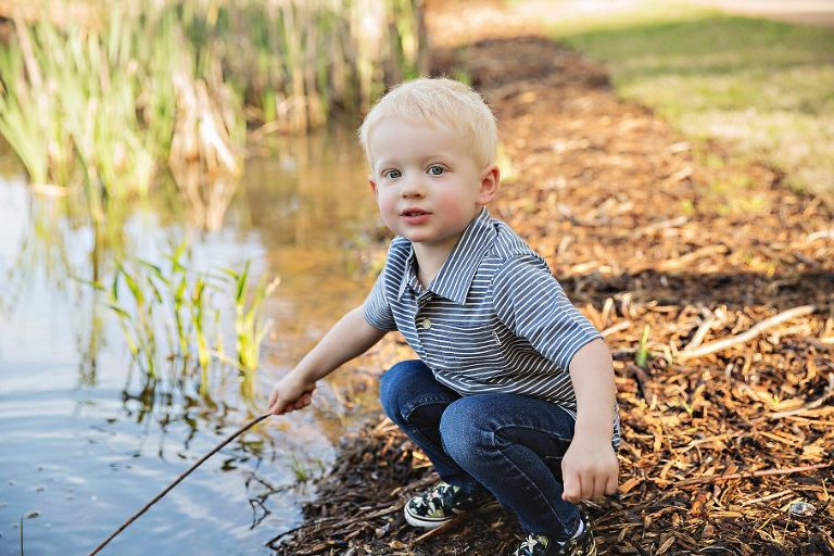 Young boy by pond holding stick