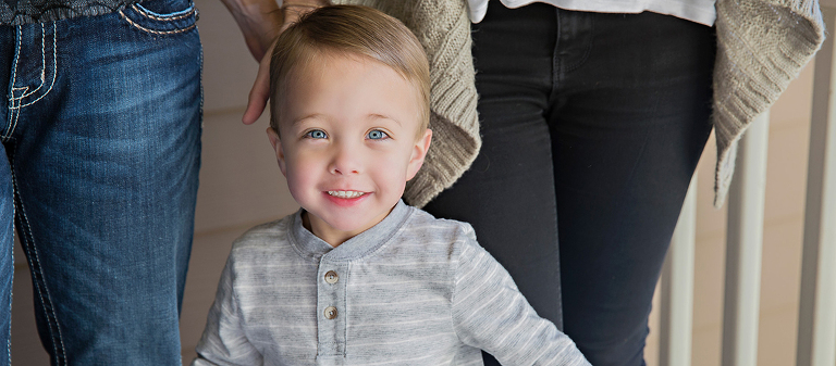 Little boy with grey shirt and blue eyes.